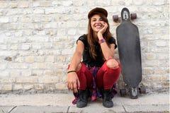 Muchacha urbana linda con sentarse que se sienta del longboard al lado de una pared de ladrillo Imagenes de archivo