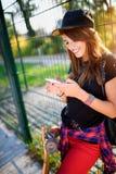 Muchacha urbana linda en parque del patín con el monopatín usando el teléfono elegante Imagenes de archivo