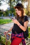 Muchacha urbana linda en skatepark con el monopatín usando el teléfono elegante Fotografía de archivo