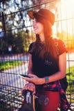 Muchacha urbana linda en skatepark con el monopatín usando el teléfono elegante Imagen de archivo