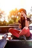 Muchacha urbana linda en skatepark con el monopatín usando el teléfono elegante Imágenes de archivo libres de regalías