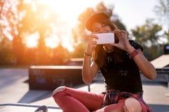 Muchacha urbana linda en skatepark con el monopatín usando el teléfono elegante Imagenes de archivo