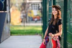 Muchacha urbana linda que sostiene el monopatín en skatepark Imagenes de archivo