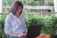 Muchacha usando el ordenador portátil, cuaderno en línea de trabajo del speac imagen de archivo libre de regalías