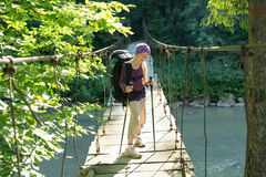 Muchacha valiente sonriente en puente colgante Foto de archivo libre de regalías