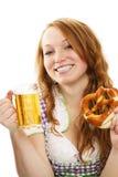 Muchacha vestida bávara feliz con la cerveza y el pretzel Imagen de archivo libre de regalías