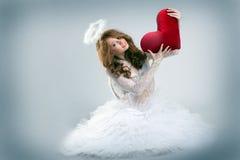 Muchacha vestida como ángel que presenta con el corazón del peluche Fotografía de archivo