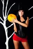 Muchacha vestida como bruja que sostiene una calabaza Imagen de archivo libre de regalías