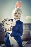 Muchacha vestida como conejo con el reloj Imágenes de archivo libres de regalías