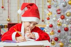 Muchacha vestida como pensamiento de Santa Claus sobre los regalos deseados de la Navidad Fotografía de archivo libre de regalías