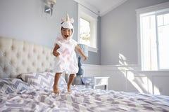 Muchacha vestida en Unicorn Costume Jumping On Bed en casa Imagen de archivo libre de regalías