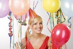 Muchacha vestida roja en partido con los globos Imagen de archivo