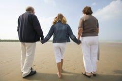 Muchacha y abuelos que recorren en la playa Fotos de archivo