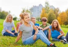 Muchacha y amigos sonrientes detrás de sentarse en hierba Imagenes de archivo