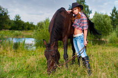 Muchacha y caballo cerca de la charca Foto de archivo