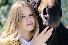 Muchacha y caballo hermosos en jardín de la primavera Foto de archivo libre de regalías