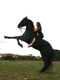Muchacha y caballo negro Imagen de archivo