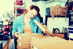Muchacha y cajas con nuevos pares de zapatos Foto de archivo libre de regalías