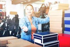 Muchacha y cajas con nuevos pares de zapatos Fotografía de archivo