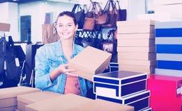 Muchacha y cajas con nuevos pares de zapatos Imagen de archivo libre de regalías
