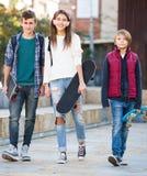 Muchacha y dos muchachos con los monopatines Fotos de archivo