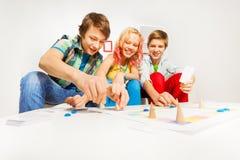 Muchacha y dos muchachos que juegan al juego de tabla en casa Foto de archivo
