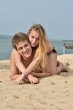 Muchacha y el hombre joven en la playa Fotos de archivo
