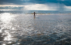 Muchacha y el mar el sol poniente y las nubes de tormenta Fotos de archivo libres de regalías