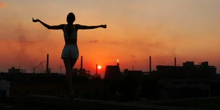 Muchacha y el Sun sobre una fábrica imagen de archivo