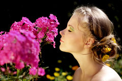 Muchacha y flores rosadas del phlox Imágenes de archivo libres de regalías