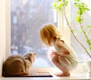 Muchacha y gato que miran fuera de la ventana Fotografía de archivo libre de regalías