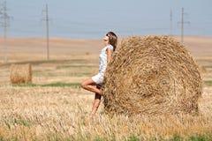 Muchacha y haystack redondo Foto de archivo libre de regalías