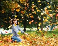 Muchacha y hojas de otoño Fotos de archivo
