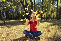 Muchacha y hojas que caen Imagen de archivo