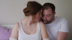 Muchacha y hombre embarazadas en sentarse blanco de las camisetas almacen de metraje de vídeo