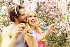 Muchacha y hombre hermoso con los o?dos del conejito que sostienen los huevos imagen de archivo libre de regalías