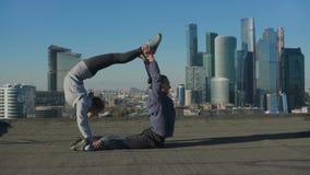 Muchacha y hombre que estiran en el tejado contra el contexto de la ciudad almacen de video