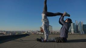 Muchacha y hombre que estiran en el tejado contra el contexto de la ciudad almacen de metraje de vídeo