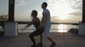Muchacha y hombres que bailan el plástico de la tira en el vídeo de la cantidad de la acción de la puesta del sol almacen de video