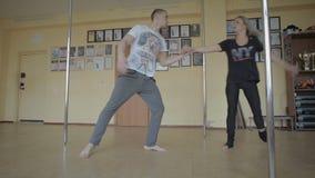 Muchacha y hombres que bailan el plástico de la tira en vídeo de la cantidad de la acción del estudio de la danza almacen de metraje de vídeo