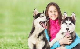 Muchacha y husky siberiano en la hierba verde Imagen de archivo libre de regalías