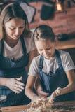 Muchacha y madre que preparan la pasta junta imagenes de archivo