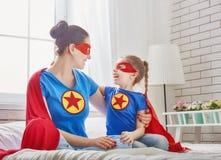 Muchacha y mamá en traje del super héroe fotos de archivo
