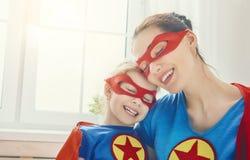 Muchacha y mamá en traje del super héroe Foto de archivo libre de regalías