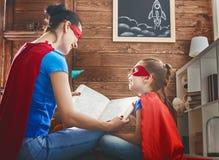 Muchacha y mamá en traje del super héroe foto de archivo