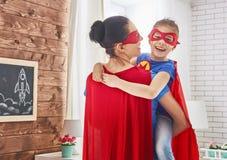 Muchacha y mamá en traje del super héroe Imagenes de archivo