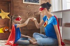 Muchacha y mamá en traje del super héroe fotos de archivo libres de regalías