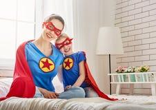 Muchacha y mamá en trajes del super héroe Fotos de archivo libres de regalías