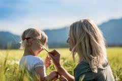 Muchacha y mamá en un campo de trigo Imágenes de archivo libres de regalías