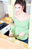 Muchacha y melón en cocina Fotos de archivo